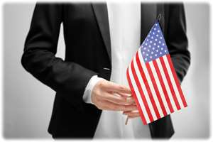 Image of a person's hands holding a United States flag, symbolizing immigration and citizenship